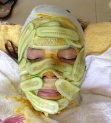 Arab AL esthetician client with cucumber facial